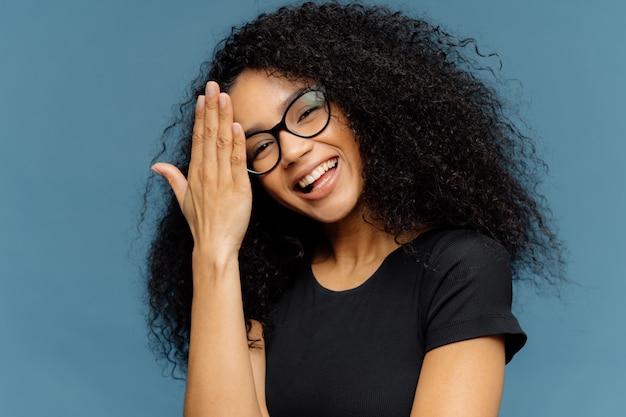 Heureuse femme afro-américaine touche le front, incline la tête, sourit joyeusement à la caméra