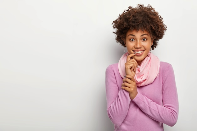 Heureuse femme afro avec une coiffure frisée, touche l'index sur les lèvres, a le sourire à pleines dents, habillée avec désinvolture