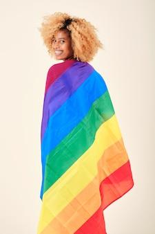 Heureuse femme afro enveloppée d'un drapeau de la fierté gaie sur un fond isolé. concept de communauté lgbtq.