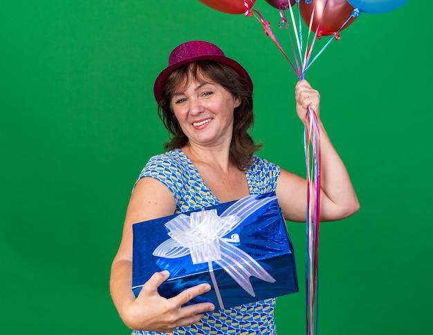 Heureuse femme d'âge moyen en chapeau de fête tenant des ballons colorés et présente souriant joyeusement célébrant la fête d'anniversaire debout sur un mur vert