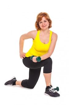 Heureuse femme d'âge moyen exerçant avec des haltères