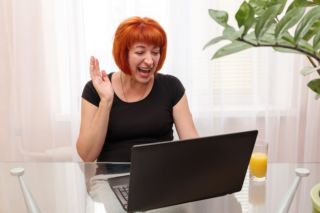 Heureuse femme d'âge moyen faisant un appel vidéo avec un ordinateur portable depuis la maison.