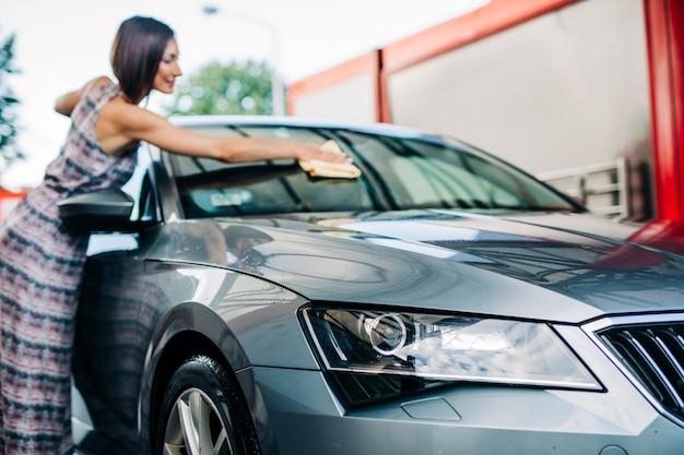 Heureuse femme d'âge moyen lavant la voiture le soir à la station de lavage de voiture.