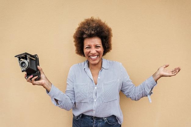 Heureuse femme âgée africaine à l'aide d'un appareil photo vintage à l'extérieur de la ville