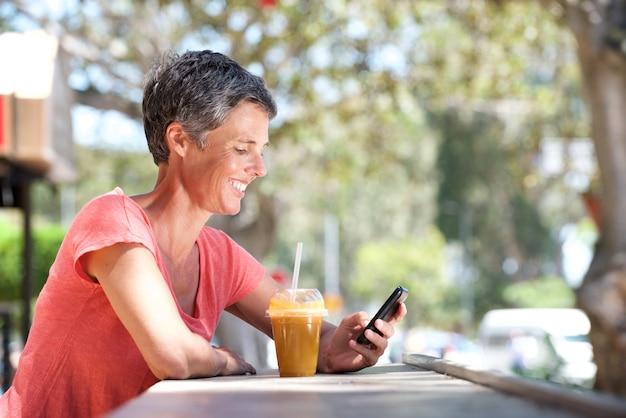 Heureuse femme âgée assis à l'extérieur avec téléphone portable et boisson