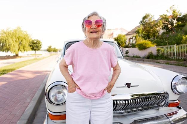 Heureuse femme âgée debout à côté de sa voiture