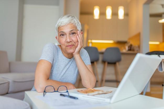 Heureuse femme âgée effectuant des paiements en ligne de facture à l'aide d'un ordinateur portable.