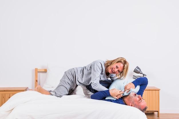 Heureuse femme âgée et homme s'amusant avec des oreillers et allongée sur le lit