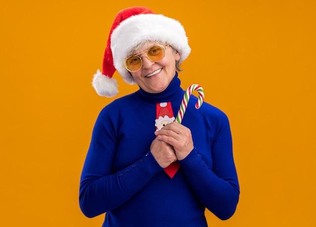 Heureuse femme âgée à lunettes de soleil avec bonnet de noel et cravate de noel tenant une canne en bonbon isolée sur un mur orange avec espace de copie