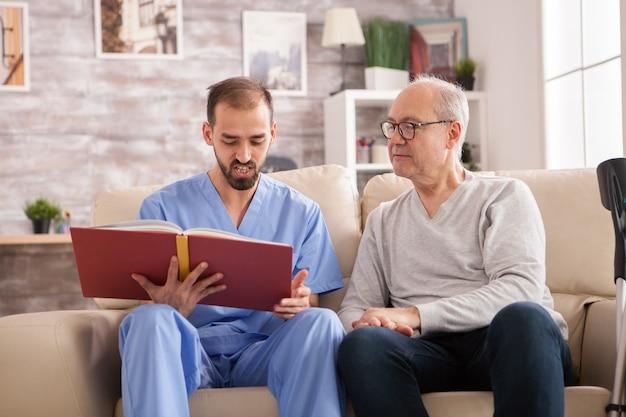 Heureuse femme âgée en maison de retraite pendant que le médecin lit un livre.
