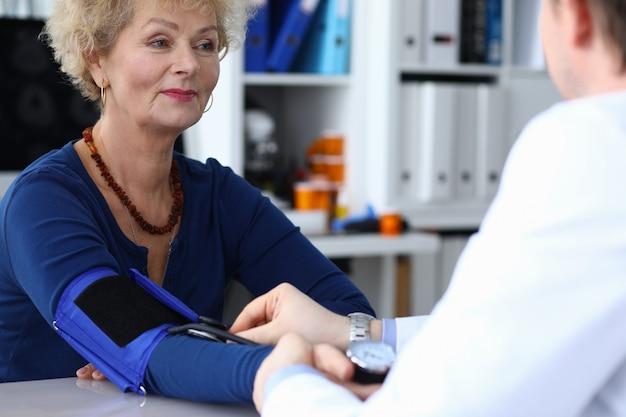 Heureuse femme âgée mesure la pression chez le médecin