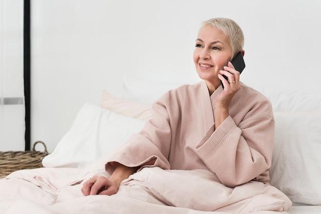 Heureuse femme âgée en peignoir parler sur smartphone au lit