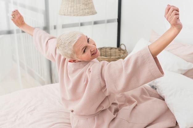 Heureuse femme âgée en peignoir qui s'étend au lit