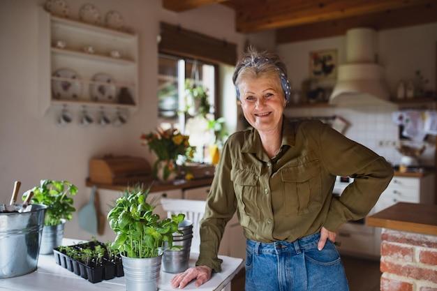 Heureuse femme âgée plantant des herbes à l'intérieur à la maison, regardant la caméra.