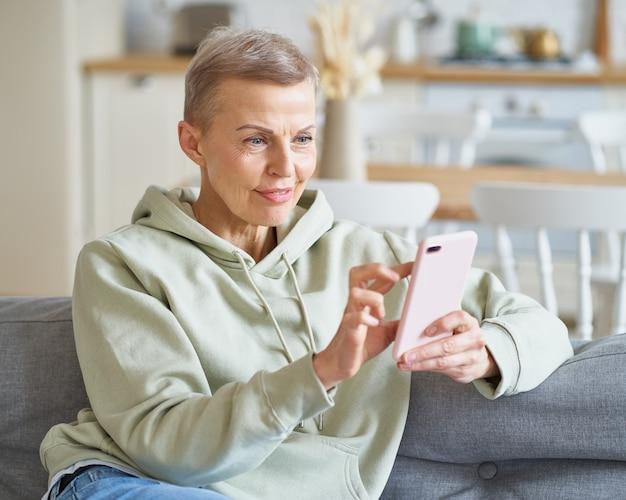 Heureuse femme âgée séduisante discutant avec un ami sur un smartphone assis sur un canapé à la maison