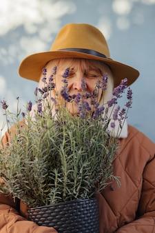 Heureuse femme âgée sentant la lavande. joyeuse femme âgée en vêtements d'extérieur à la mode et chapeau souriant