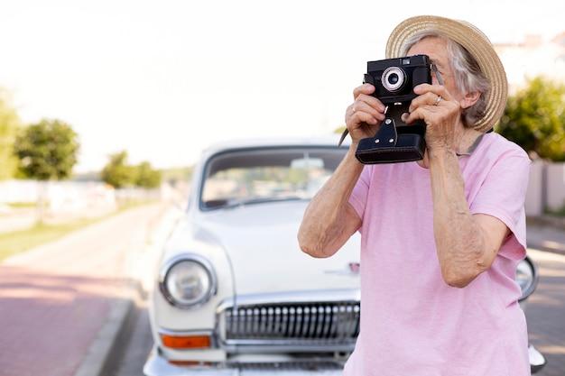 Heureuse femme âgée tenant un appareil photo en voyage