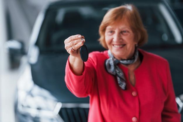 Heureuse femme âgée en tenue de soirée se tient devant une voiture blanche moderne.