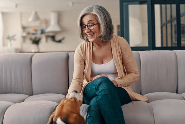 Heureuse femme âgée en vêtements décontractés passant du temps avec son chien assis sur le canapé à la maison