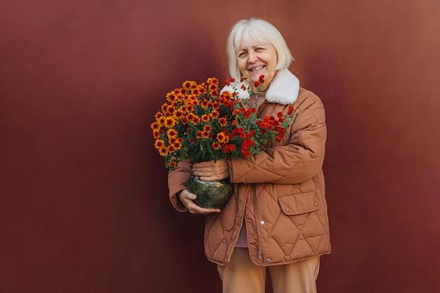 Heureuse femme âgée en vêtements d'extérieur souriante pour la caméra et portant des fleurs en pot le jour du printemps.
