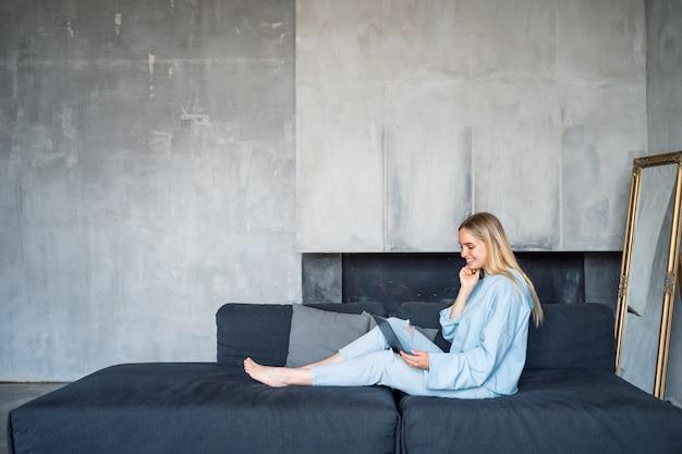 Heureuse femme à l'aide d'un ordinateur portable argenté assis sur un canapé
