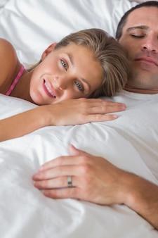 Heureuse femme allongée sur la poitrine des maris au lit