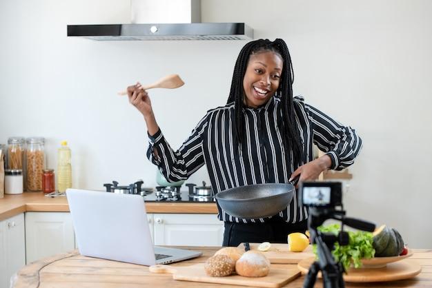 Heureuse femme américaine africaine vlogger diffusant la cuisson de la vidéo en direct à la maison