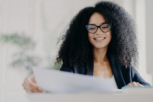 Heureuse femme américaine afro avec une coiffure frisée, regarde à travers des documents