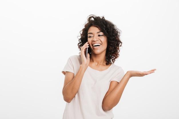 Heureuse femme américaine avec une coiffure afro portant un t-shirt parlant sur smartphone et faisant des gestes de côté, isolé sur un mur blanc