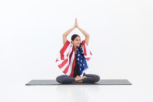Heureuse femme américaine yogi faisant des exercices d'étirement de yoga assis sur un tapis, avec drapeau américain, sur une scène blanche en studio. 4 juillet concept de la fête de l'indépendance de l'amérique