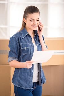 Heureuse femme appelant une entreprise de transport pour déménager dans une nouvelle maison.