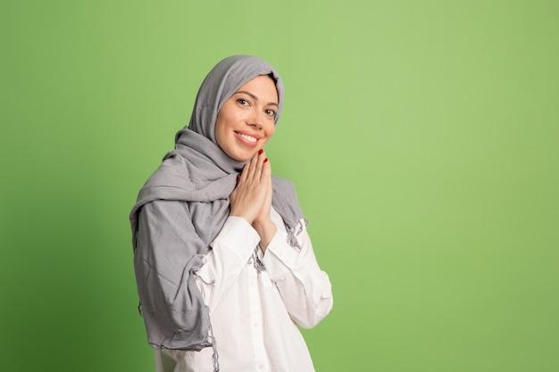 Heureuse femme arabe en hijab. portrait de jeune fille souriante, posant au studio vert.