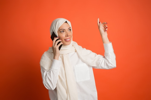 Heureuse femme arabe en hijab avec téléphone portable. portrait de jeune fille souriante, posant au fond de studio rouge.
