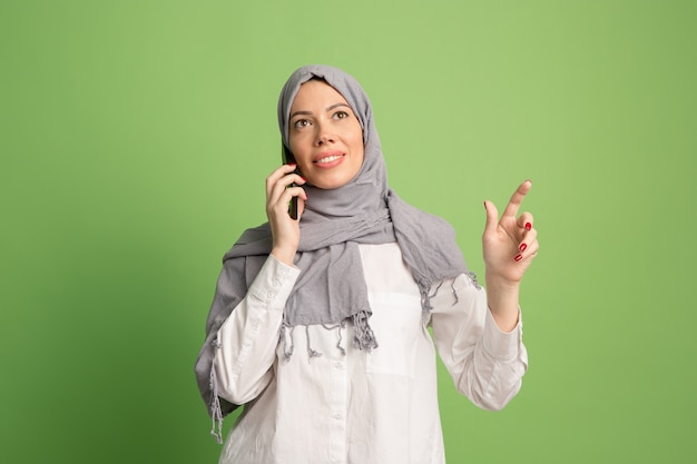 Heureuse femme arabe en hijab avec téléphone portable. portrait de jeune fille souriante, posant au fond de studio vert. jeune femme émotionnelle. émotions humaines, concept d'expression faciale. vue de face.