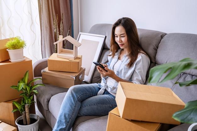 Heureuse femme asiatique à l'aide de smartphone dans le salon avec de nombreuses boîtes