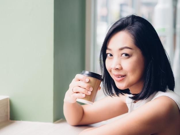 Heureuse femme asiatique boit une tasse de café chaud dans une atmosphère paisible