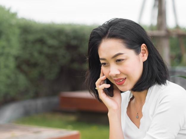 Heureuse femme asiatique a de bonnes nouvelles au téléphone.