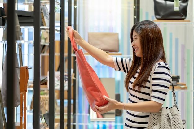Heureuse femme asiatique en choisissant le magasin de sacs femme avec une action heureuse au centre du département