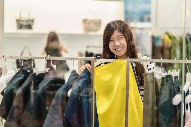 Heureuse femme asiatique en choisissant des vêtements et jupe dans un magasin de verre