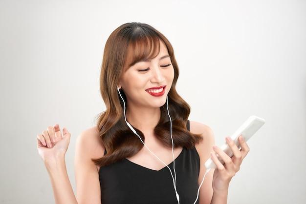 Heureuse femme asiatique écoutant de la musique sur les écouteurs. jeune modèle féminin asiatique frais