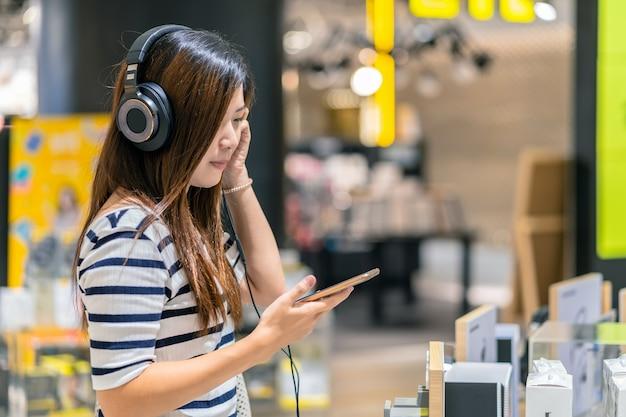 Heureuse femme asiatique à l'écoute et la technologie de test écouteur ou un casque