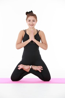 Heureuse femme asiatique faisant stha padmasana pose avec les mains jointes et les yeux fermés tout en méditant.