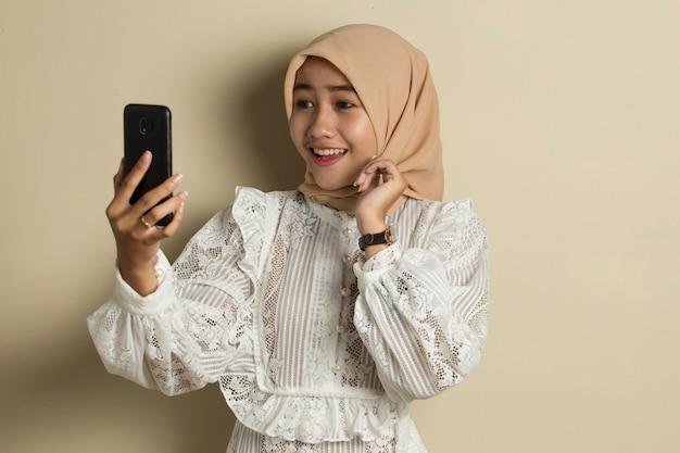 Heureuse femme asiatique en hijab avec téléphone portable faisant un appel vidéo.