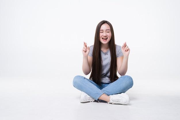 Heureuse femme asiatique joyeuse assise sur le sol et avec les doigts croisés isolés sur mur gris