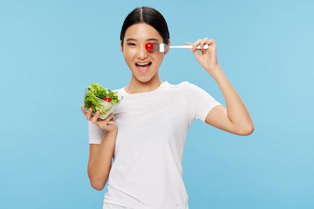 Heureuse femme asiatique mangeant une salade saine, concept de régime