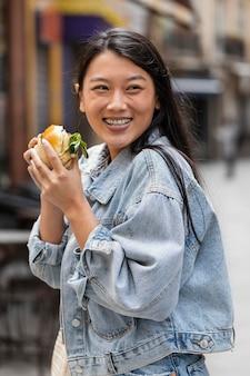 Heureuse femme asiatique, manger un hamburger à l'extérieur
