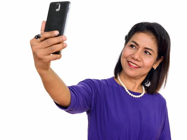 Heureuse femme asiatique mature prenant selfie isolé contre le mur blanc