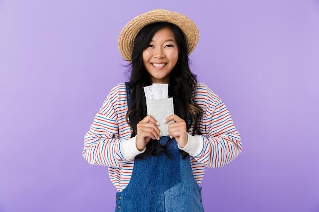 Heureuse femme asiatique posant isolé sur mur violet tenant un passeport et des billets