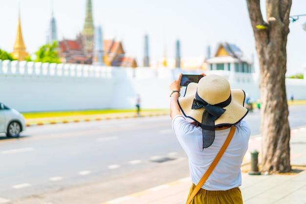Heureuse femme asiatique prenant une photo du temple