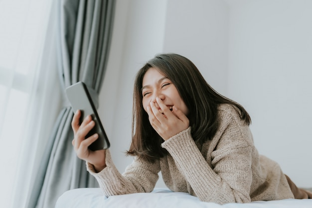 Heureuse femme asiatique profiter à l'aide de smartphone